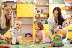 Kindertagesstättenkinder, die mit Lehrer und Helfer im Klassenzimmer spielen lizenzfreies stockbild