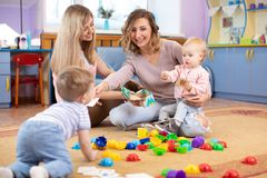 Kindertagesst?ttenkinder, die mit Spielwaren spielen Mütter um ihre Kinder mitteilen und sich kümmern stockfoto