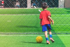 Kindertröpfelnder Fußball auf einem Feld lizenzfreies stockfoto