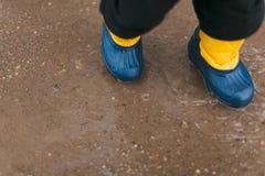 Kindertragende Stiefel eine Pfütze stockbild