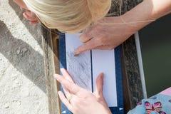 Kinderuhren als Erwachsenes ätzt Zeichnung auf Papieraußenseite Lizenzfreies Stockfoto