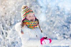 Kindervoedingsvogel in de winterpark Jonge geitjesspel in sneeuw aard en royalty-vrije stock foto's