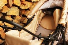 Kinderwagen auf dem Hintergrund des Staplungsbrennholzes stockbilder