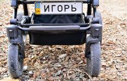 Kinderwagen (Spaziergänger) mit Kfz-Kennzeichen mit dem Namen des Babys auf dem Bodenhintergrund Stockfotografie