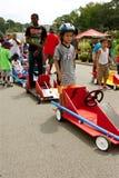 Kinderwartezeit durch Autos bevor dem Laufen im Seifenkistenrennen Stockfotos