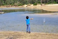 Kinderwerfender Stein im Wasser Lizenzfreie Stockbilder