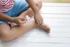 Kinderwunde auf Bein und dem Druging verwundet auf hölzernem weißem Hintergrund, Draufsicht Lizenzfreie Stockfotografie