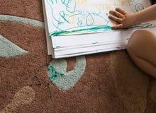 Kinderzeichnung auf Papier u. Teppich Lizenzfreies Stockfoto