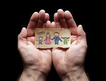 Kinderzeichnung der Familie mit dem Schutz von schalenförmigen Händen lizenzfreie stockfotografie