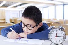 Kinderzeichnung in der Klasse mit einer Uhr auf Schreibtisch Stockfotografie