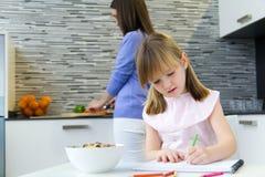 Kinderzeichnung mit Zeichenstiften, Sitzen bei Tisch in der Küche Lizenzfreie Stockfotos