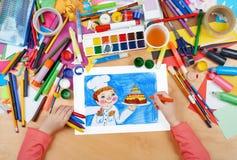Kinderzeichnungs-Feiertagskuchen und Koch, Draufsichthände mit Bleistiftmalereibild auf Papier, Grafikarbeitsplatz Lizenzfreie Stockfotografie