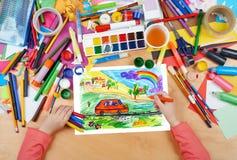 Kinderzeichnungs-Hundereise im Auto, Draufsichthände mit Bleistiftmalereibild auf Papier, Grafikarbeitsplatz Stockfotografie
