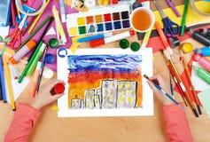 Kinderzeichnungs-Nachtstadt, Draufsichthände mit Bleistiftmalereibild auf Papier, Grafikarbeitsplatz Stockbild