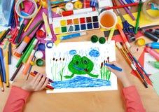 Kinderzeichnungsfrosch im Fluss, Draufsichthände mit Bleistiftmalereibild auf Papier, Grafikarbeitsplatz Stockbilder