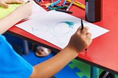Kinderzeichnungsperson auf Papier Stockfotos