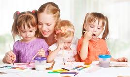 Kinderzwillingsschwestern zeichnen Farben mit ihrer Mutter im Kindergarten lizenzfreie stockbilder