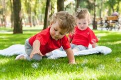 Kinderzwillingsspiel auf dem Gras Lizenzfreie Stockfotos