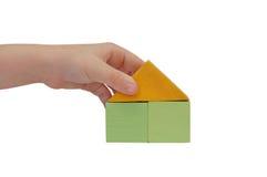 Kindhand bilden ein Gebäude mit farbigen Blöcken Stockfotos