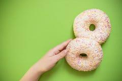 Kindhand die de laatste doughnut van de doos stelen Smakelijke zoete donuts op groene achtergrond Ongezond suikerdessert stock afbeelding