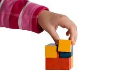 Kindhand, die einen Würfel der farbigen Blöcke aufbaut Stockbilder