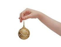 Kindhand, die goldene Weihnachtskugel anhält Lizenzfreie Stockfotografie