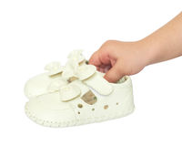 Kindhand hält kleine weiße Babyschuhe an Stockbilder