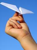 Kindhand mit Papierflugzeug lizenzfreie stockfotos