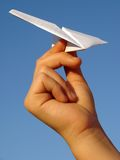 Kindhand mit Papierflugzeug stockfotografie