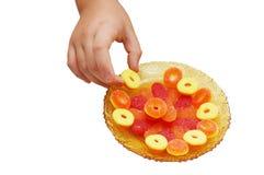 Kindhand nehmen eine Süßigkeit von einem Saucer mit Süßigkeiten Stockfotos
