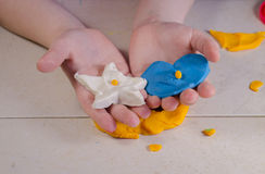 Kindhanden en plasticine Stock Foto