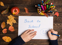 Kindhanden, kleurpotloden, appel en terug naar schoolteken op houten Royalty-vrije Stock Foto's
