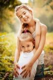 Kindheit, Familie, Freundschaft und Leutekonzept - zwei glückliche Kinderschwestern, die draußen umarmen lizenzfreies stockfoto