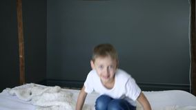 Kindheit, Junge springt auf Bett in der Zeitlupe und betrachtet in camera Schlafzimmer stock footage
