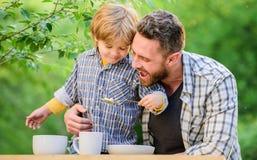 Kindheitsgl?ck Gl?cklicher Vatertag Wenig Junge mit dem Vati im Freien Gesundes Lebensmittel und N?hren Familientag Sohn und lizenzfreie stockfotografie