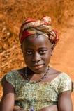 Kindia, Guiné - 28 de dezembro de 2013: Retrato de menina africana não identificada com a estrada de terra vermelha no fundo Fotos de Stock