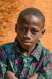 Kindia, Guinea - 28 de diciembre de 2013: Retrato del muchacho africano no identificado con el camino de tierra rojo en fondo Imagen de archivo