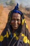 Kindia, gwinea - Grudzień 27, 2013: Niezidentyfikowana afrykanina Futa kobieta z zakrywającą droga gruntowa, włosy i dziki ogień  Fotografia Royalty Free