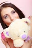 Kindisches infantiles Mädchen der jungen Frau im rosa küssenden Teddybärspielzeug Lizenzfreie Stockfotos