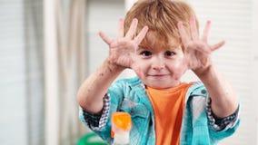 Kindjongen die met zijn vuile handen na het spelen in vuil en het tuinieren van de lenteinstallaties pronken de ring bloeit thuis stock video