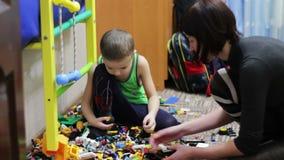 Kindjongen en zijn Moeder die met Speelgoed spelen stock footage