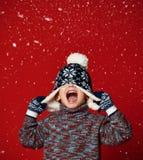 Kindjongen in gebreide hoed en sweater en vuisthandschoenen die pret over kleurrijke rode achtergrond hebben royalty-vrije stock fotografie