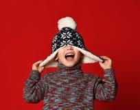 Kindjongen in gebreide hoed en sweater en vuisthandschoenen die pret over kleurrijke rode achtergrond hebben royalty-vrije stock foto