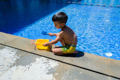 Kindjongen het spelen met zijn speelgoed op de rand van een zwembad Stock Foto