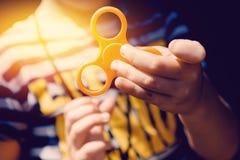 Kindjongen om met Fidget Spinner in zijn handen te spelen, het concept het verlichten van spanning, royalty-vrije stock foto