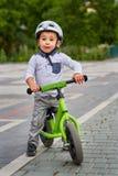 Kindjongen in witte helm die op zijn eerste fiets met een helm berijden fiets zonder pedalen stock foto