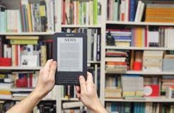 Kindle ebook. Ebook reading device and library background Stock Images