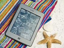 Kindle Touch EReader At The Beach. With a screen that works in bright sun, this Kindle Touch e-reader is handy for summer beach reading.  Today's electronic e Royalty Free Stock Photography