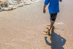 Kindlooppas door de branding van een zandig strand royalty-vrije stock afbeeldingen