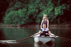 Cute girl staying near rowing guy on boat royalty free stock photo